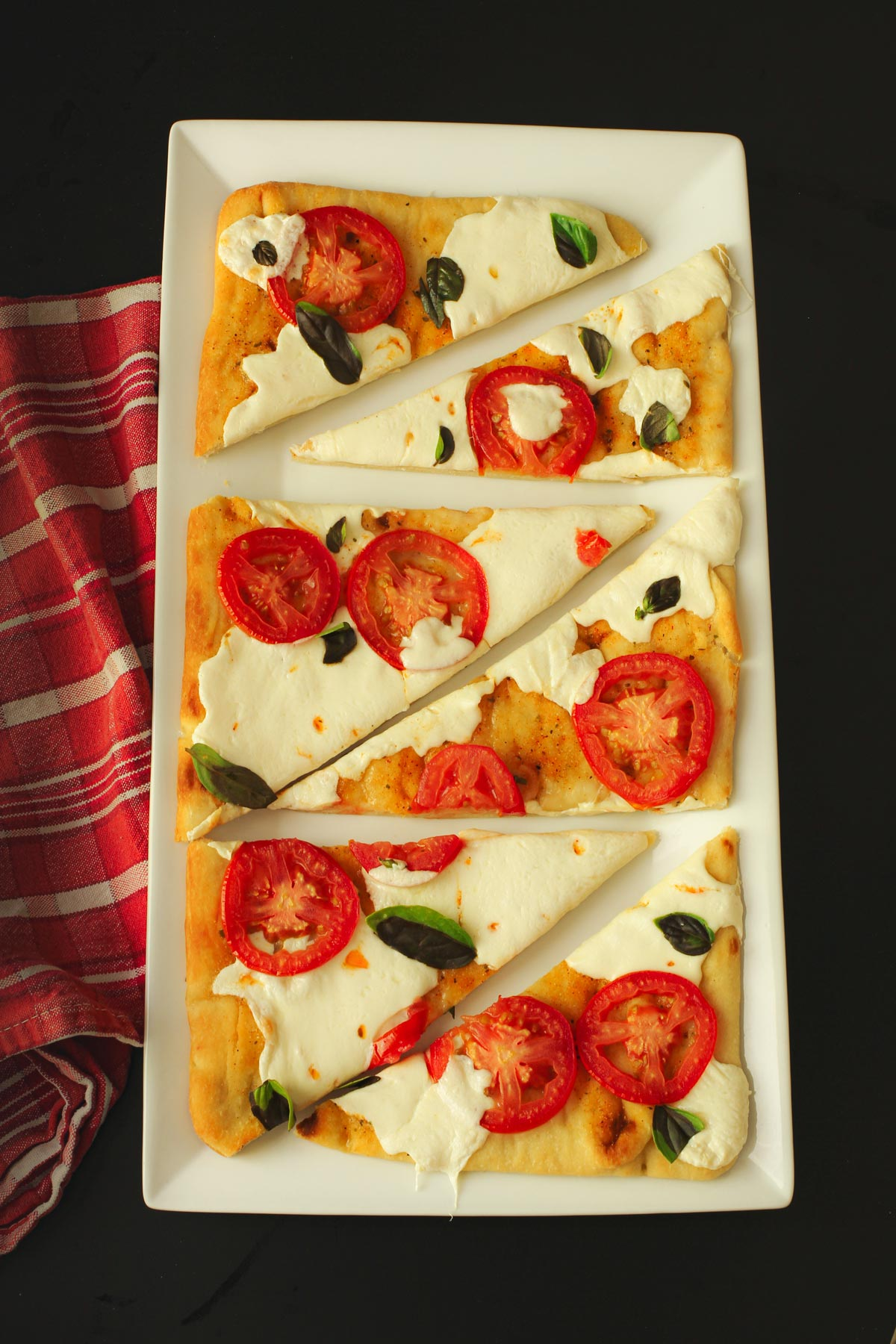 margherita flatbread pizza cut into wedges on white tray with red cloth.