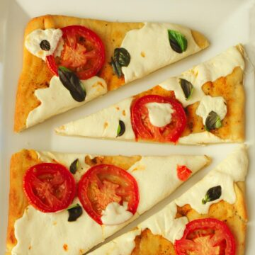 margherita flatbread pizza cut into wedges on a platter.
