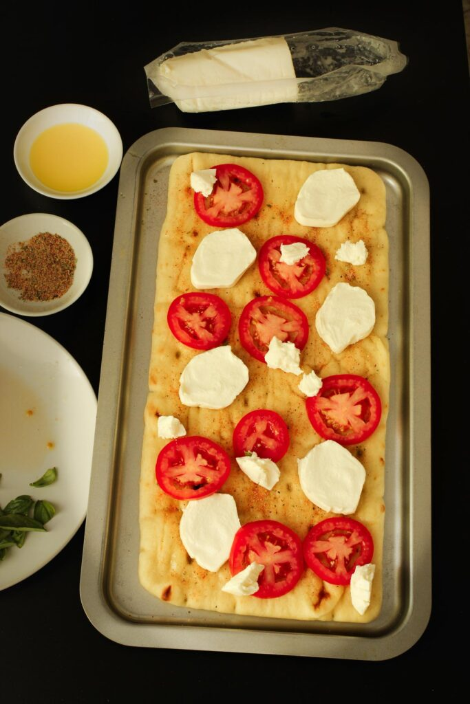 tomatoes and mozzarella slices distributed across the surface of the flatbread.