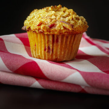 raspberry muffin on red and white checked napkin on black tabletop.