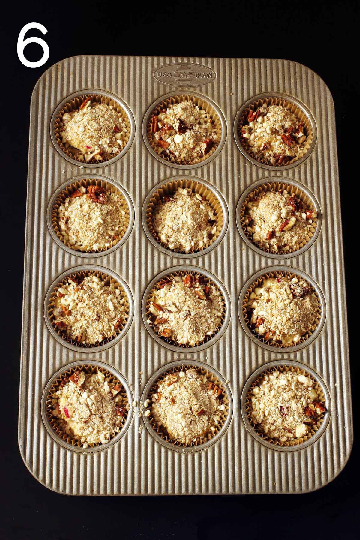 unbaked muffins with streusel on them ready to bake.