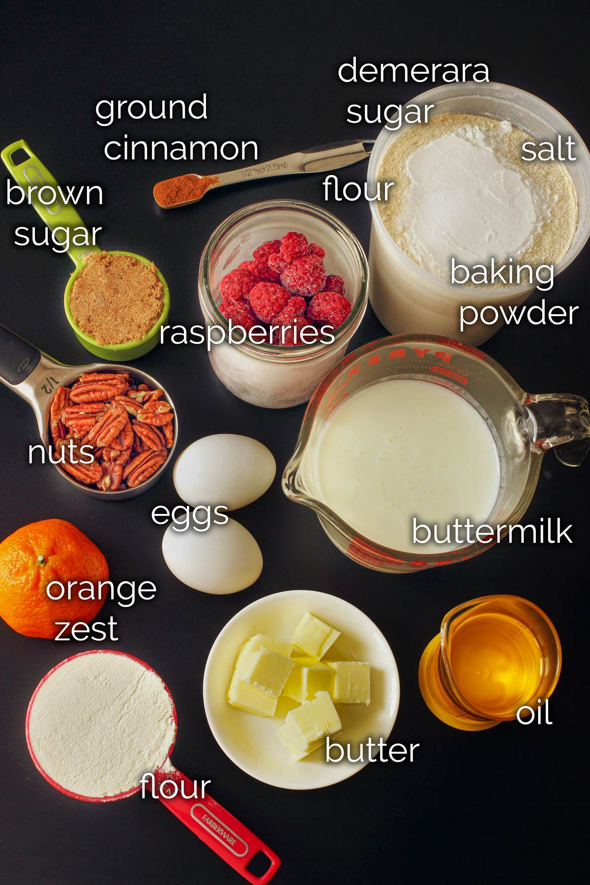 ingredients for raspberry muffins on a black tabletop.