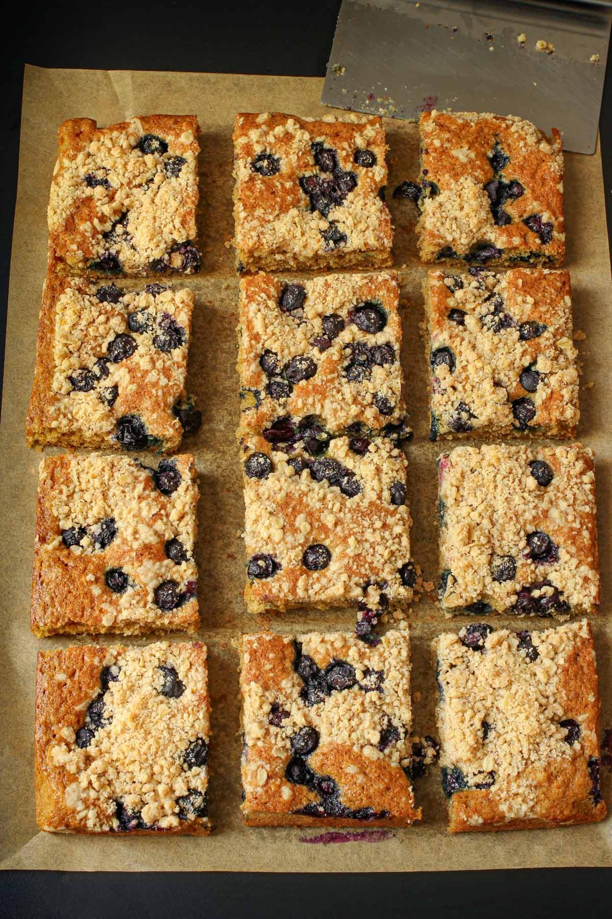baked Blueberry Lemon Coffee Cake cut into squares on brown parchment paper.