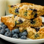 stacked squares of blueberry lemon coffeecake on a plate with blueberries with glasses of milk in background.