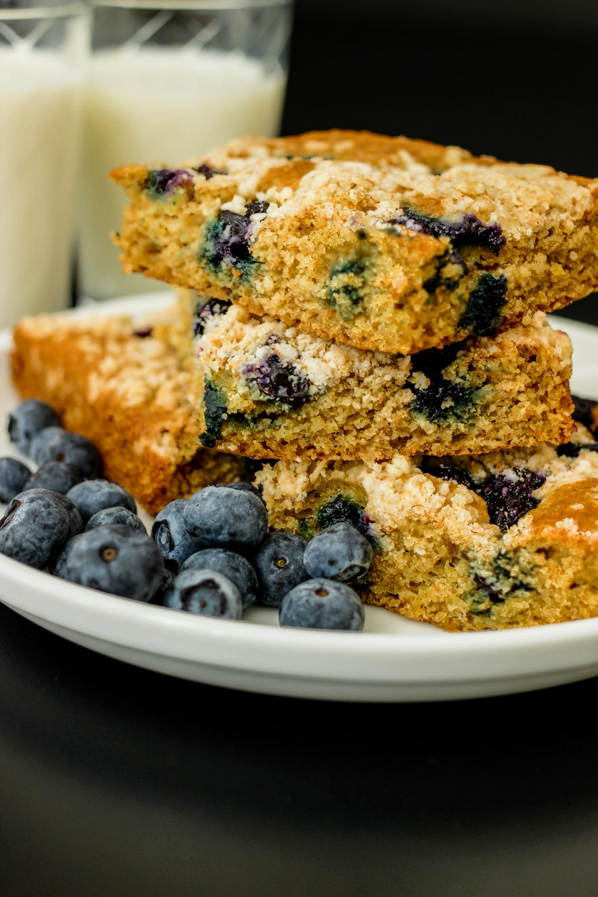 stack of blueberry coffee cake squares on a white plate.