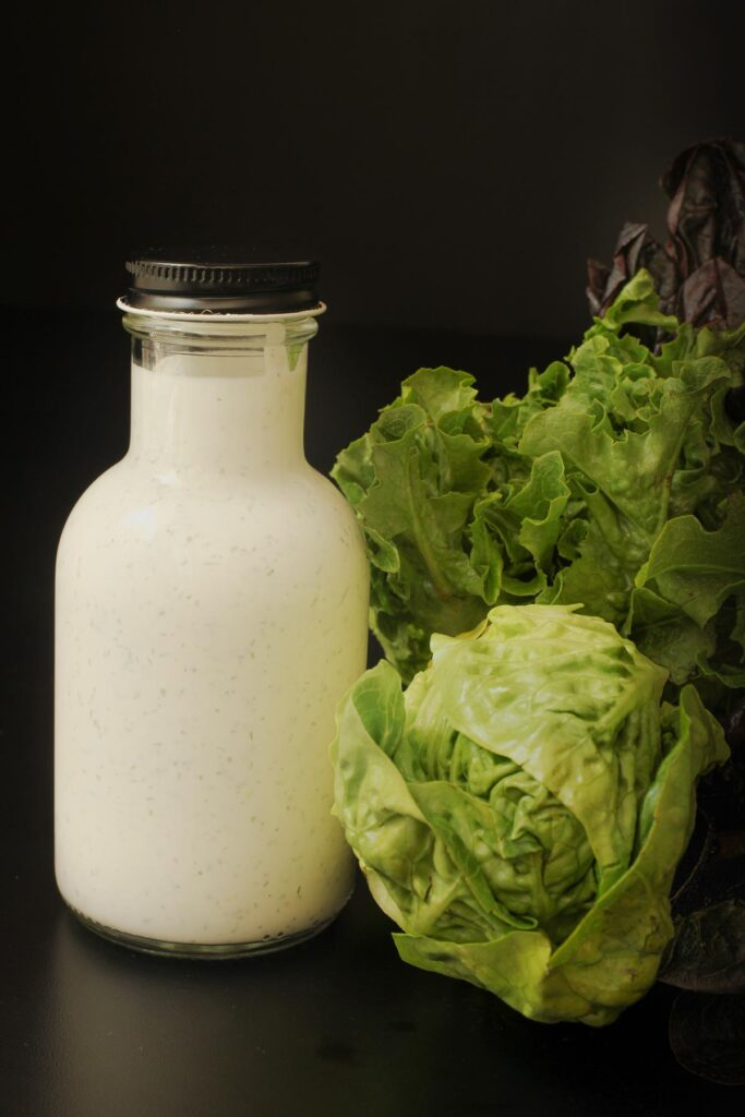 the completed dressing a small glass bottle next to a head of lettuce.