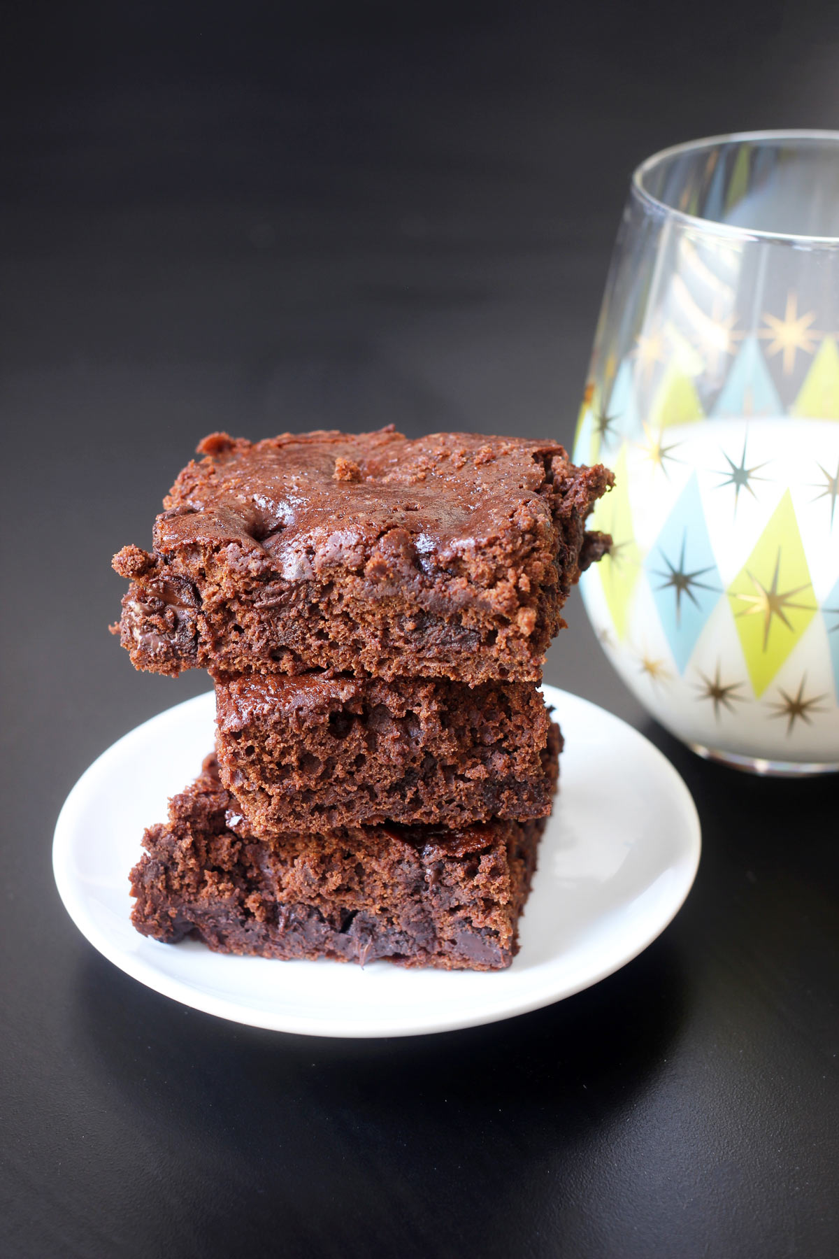 brownies stacked on small white plate next to glass of milk.
