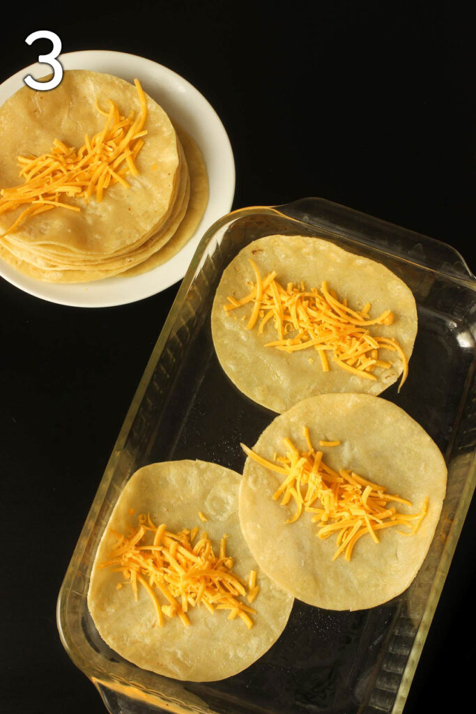 tortillas laid out on baking dish and plate with cheese lined up in the middle.