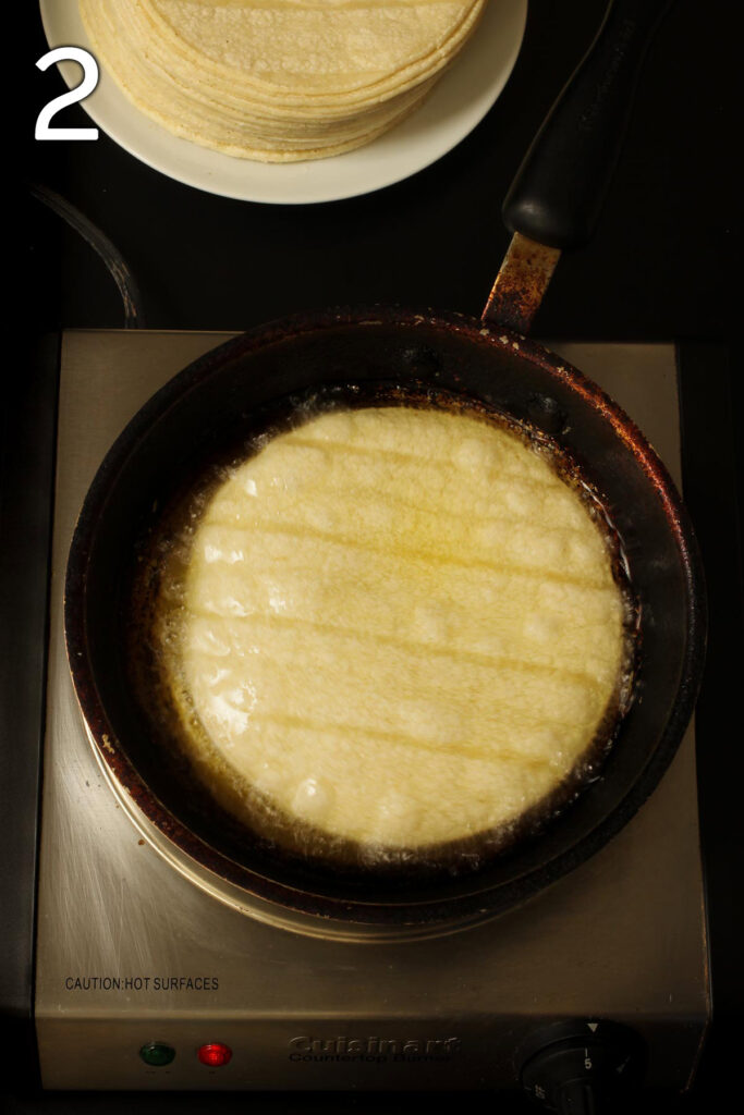 skillet on medium heat with hot oil and corn tortilla frying.