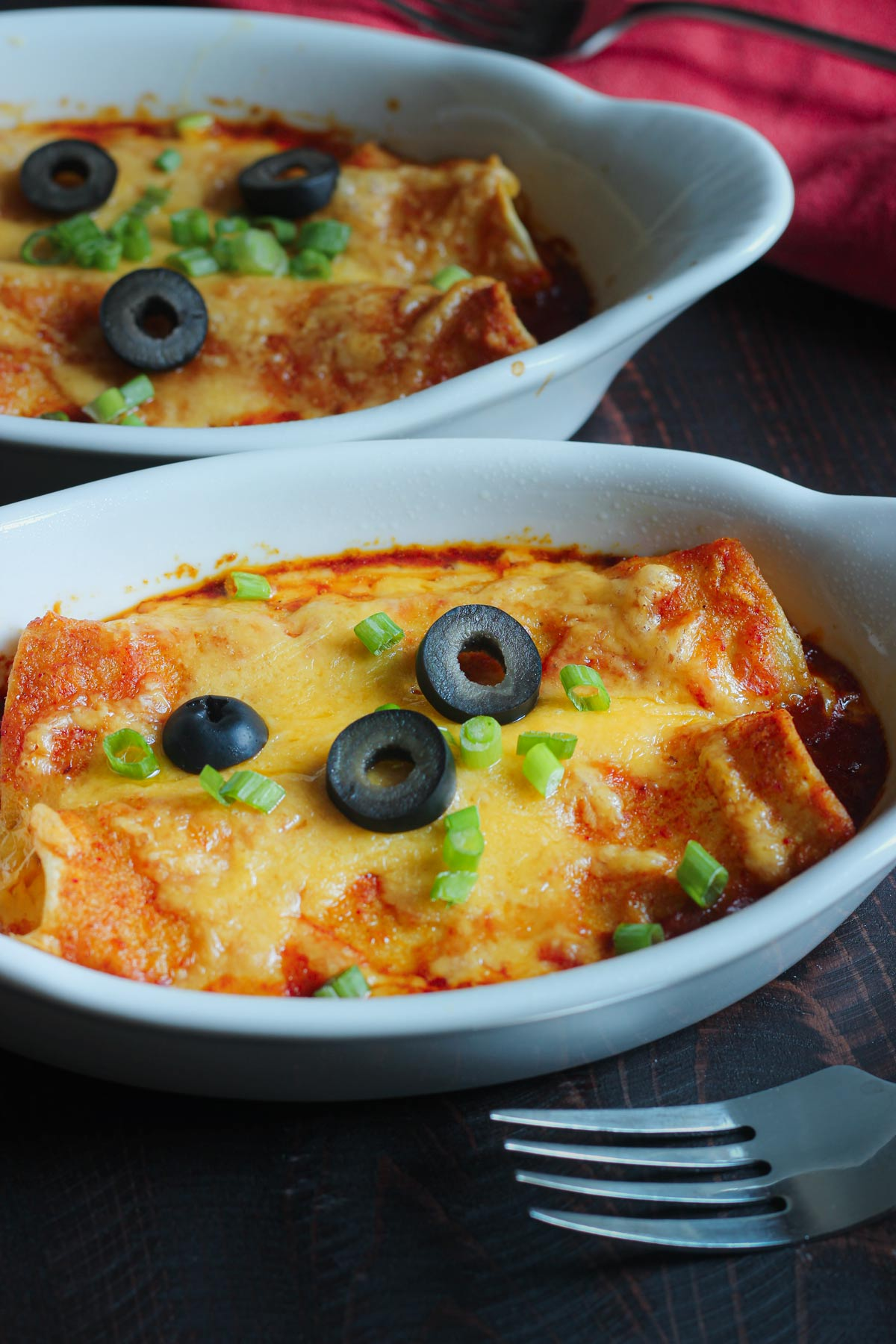gratin dishes each holding two cheese enchiladas topped with sliced olives and green onions.