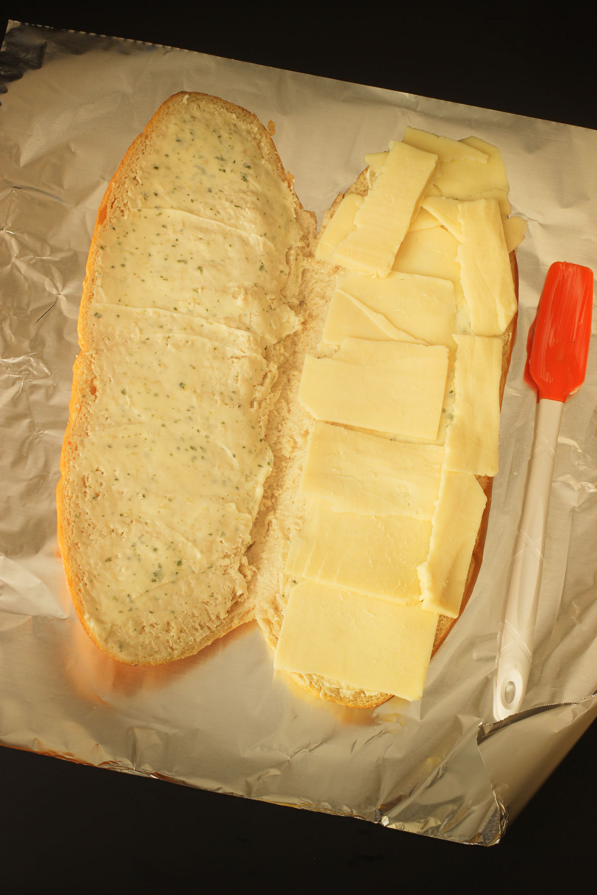 cheese layered on one side of the large French loaf on the sheet of aluminum foil.