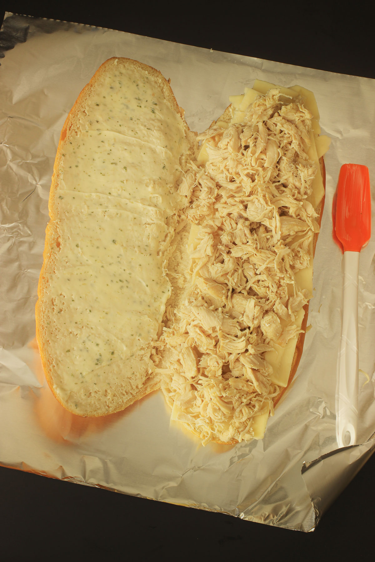 chicken piled on the cheese on one side of the large French loaf.