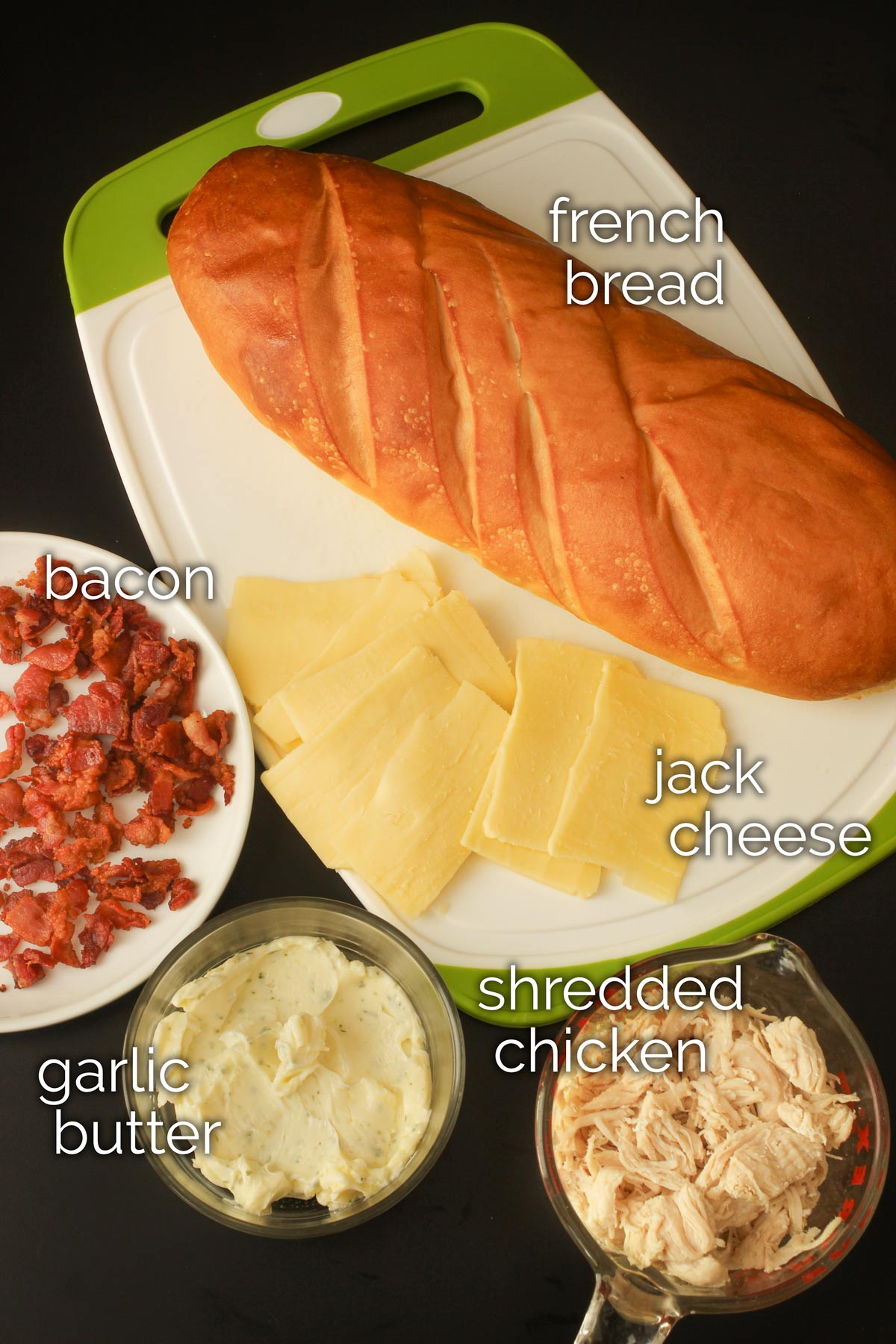 ingredients for hot chicken sandwiches laid out on black tabletop.