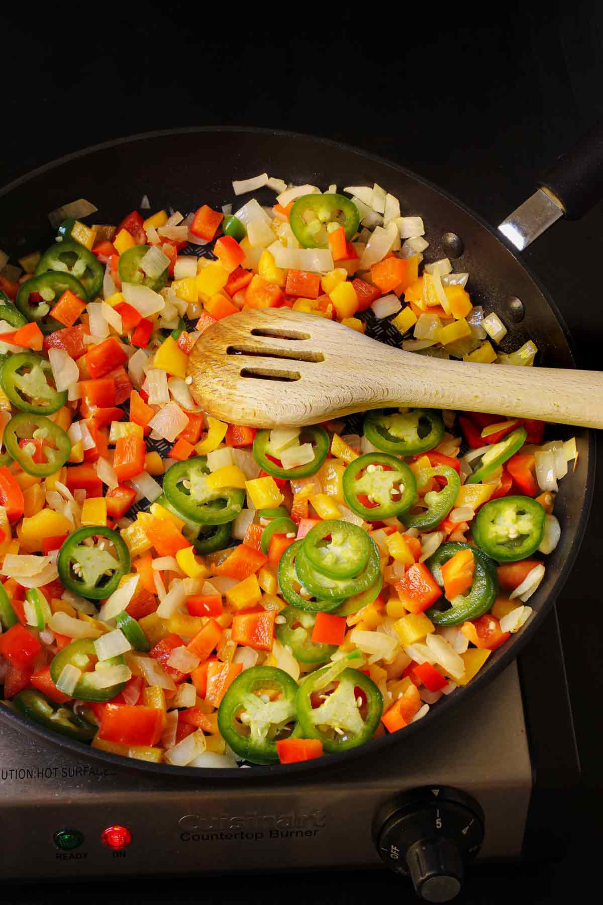 the cooked vegetables in the skillet with a wooden spoon.