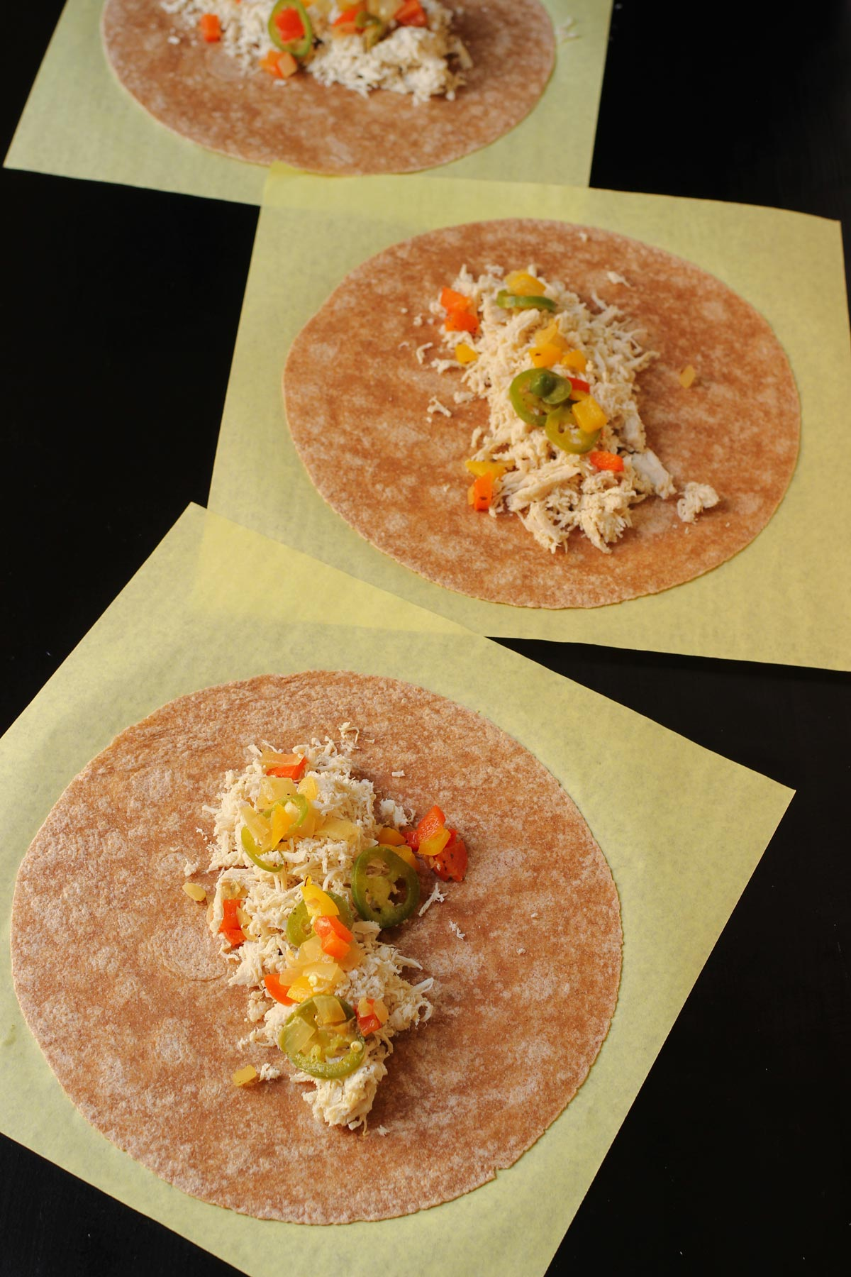 fajita vegetable mixture layered atop chicken layer in assembly line.
