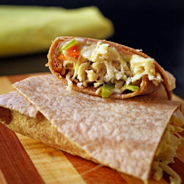 chicken fajita burrito cut in half with one half resting on the other, showing the cut side.