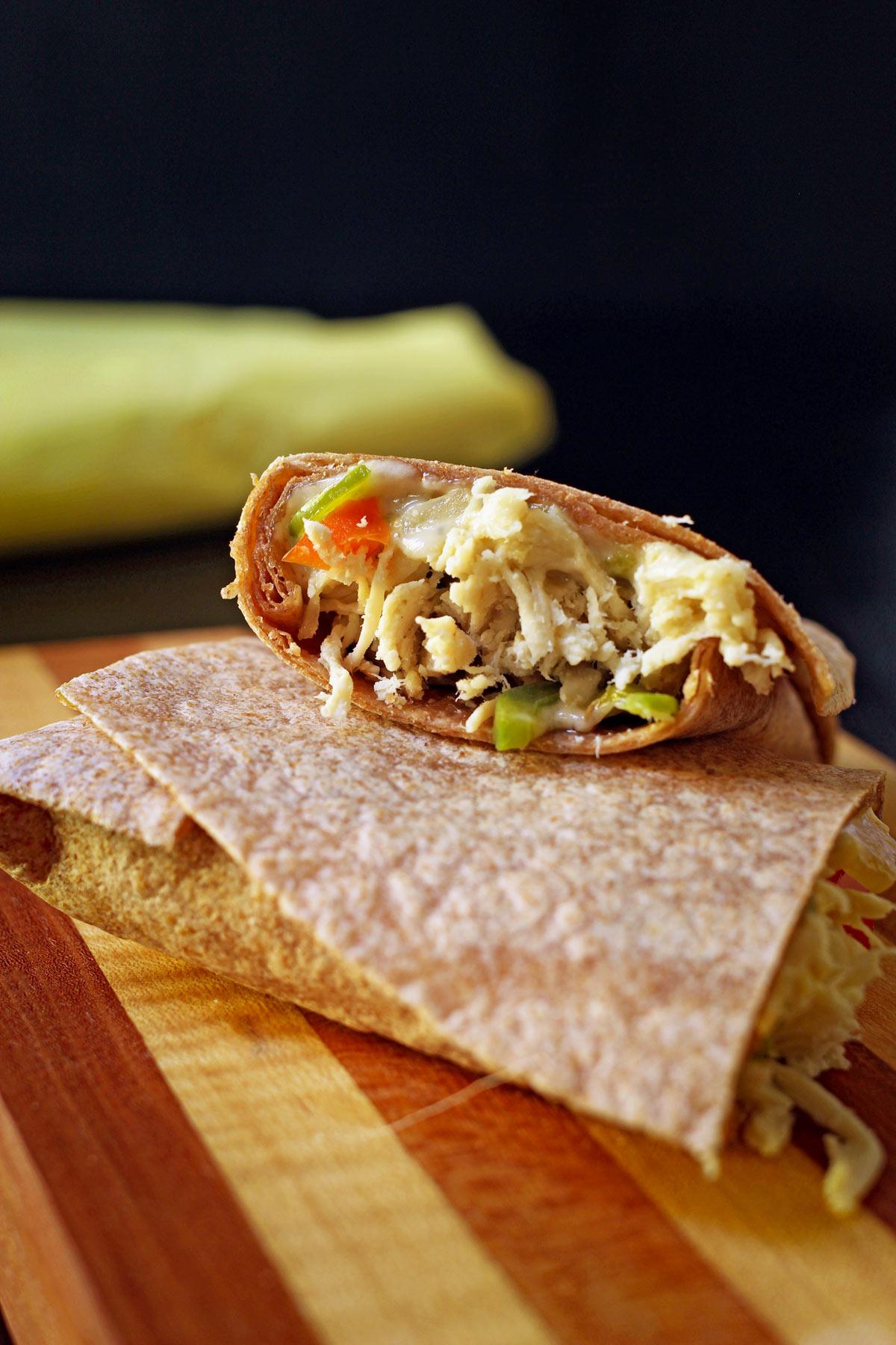 close up view of the cut side of a fajita burrito bursting with shredded chicken, fajita veggies, and cheese.