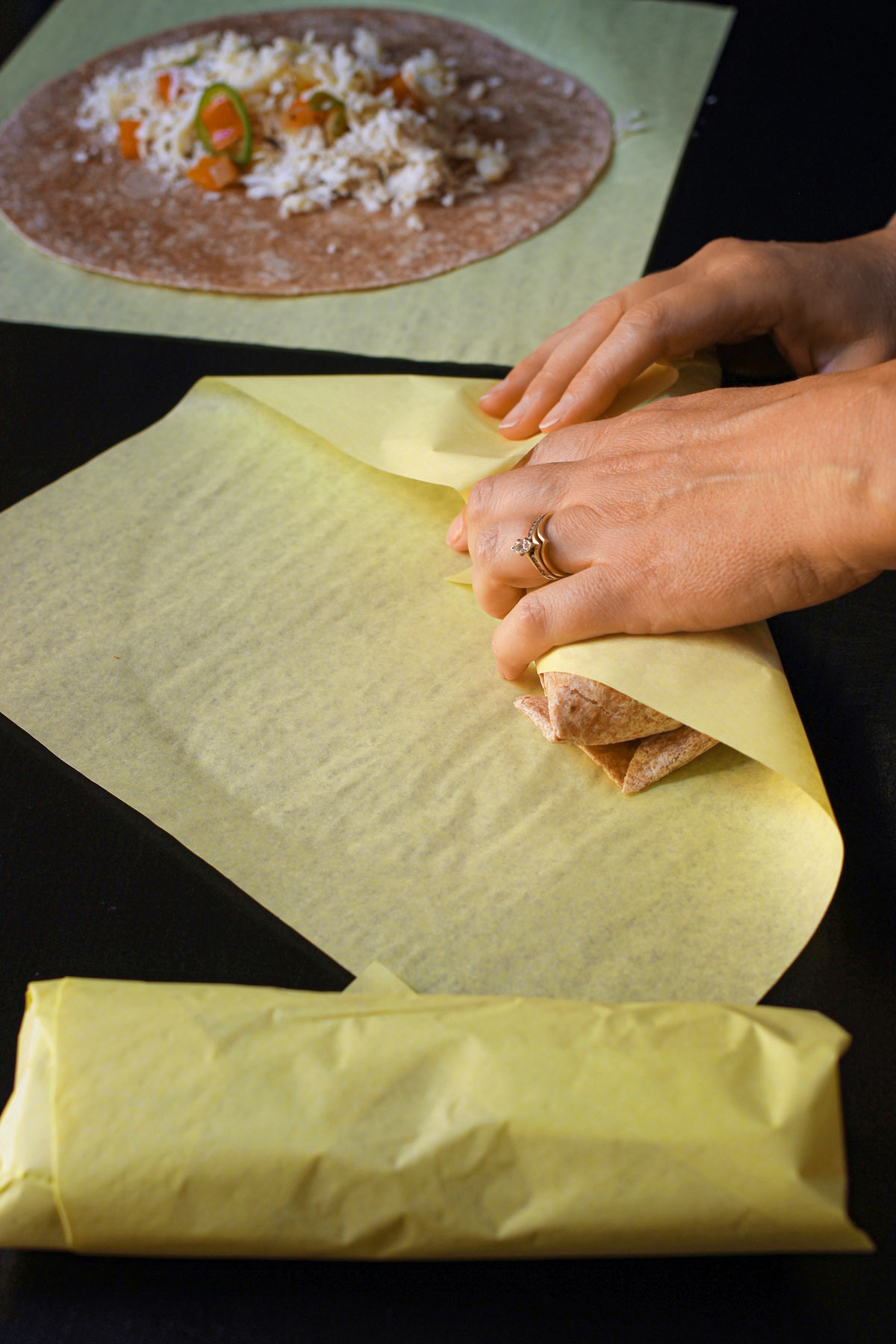 hands wrapping the rolled burrito in a deli wrap.