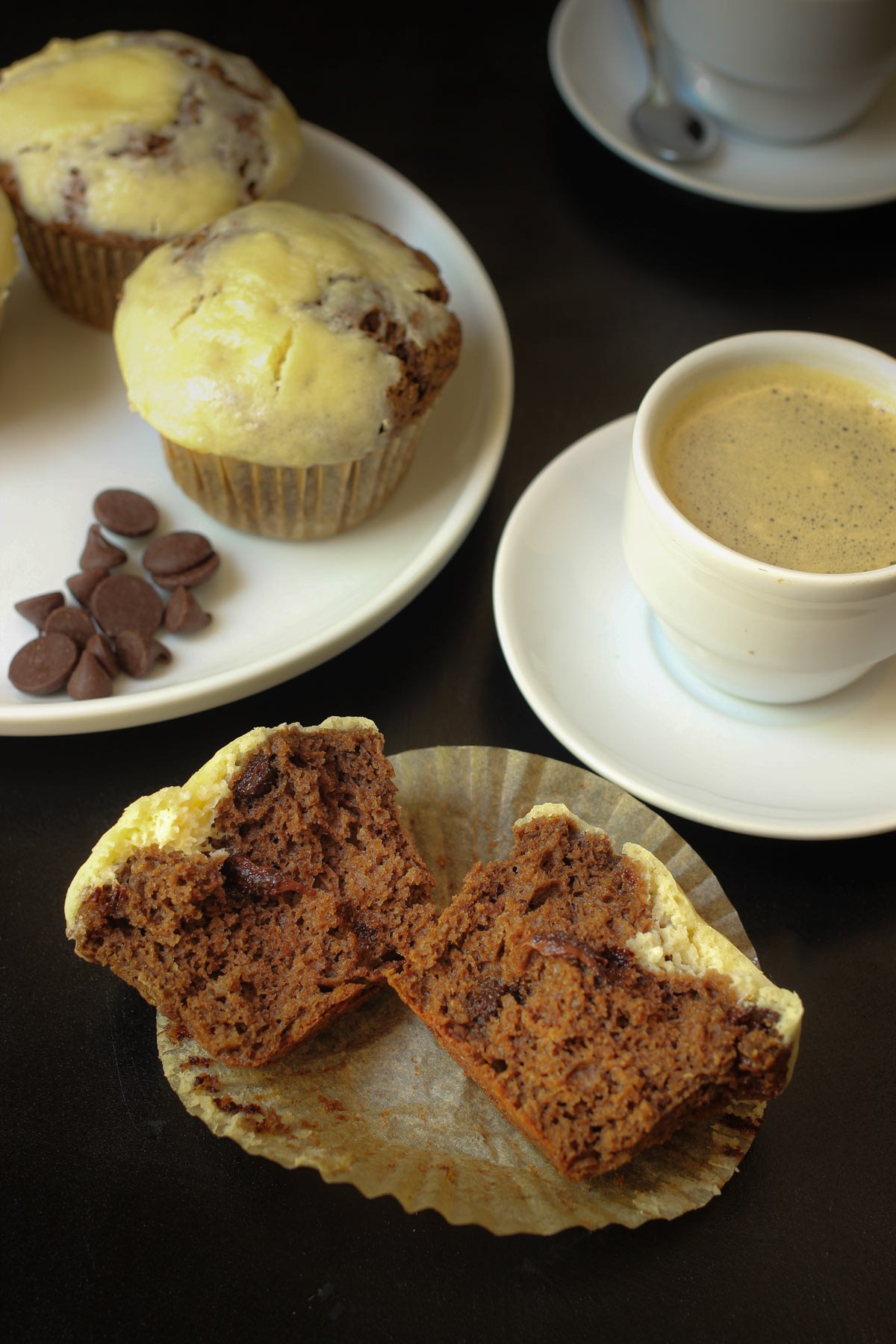 split chocolate cream cheese muffin on its wrapper next to espresso and plate of muffins.