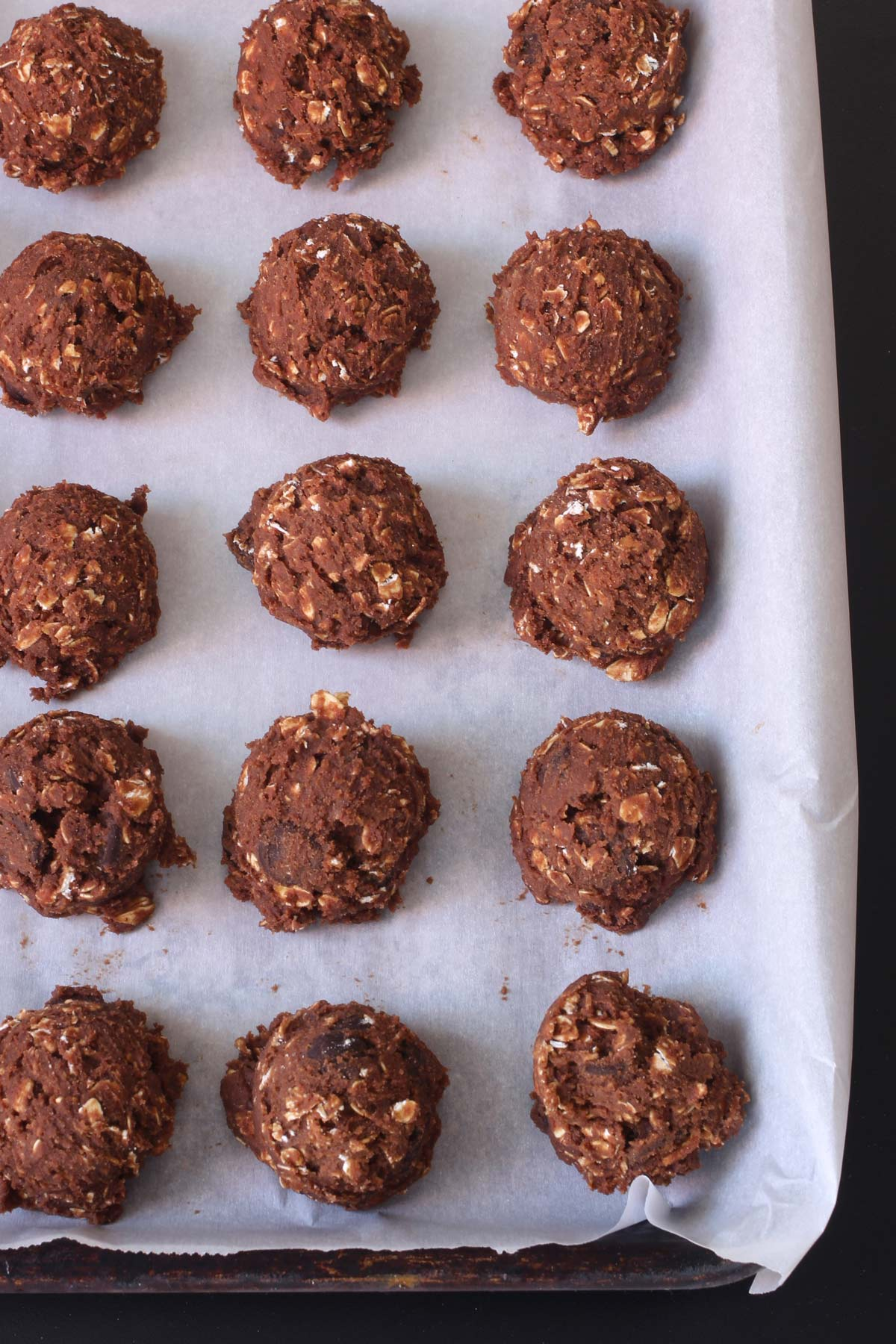chocolate cookie dough balls on a parchment-lined tray.