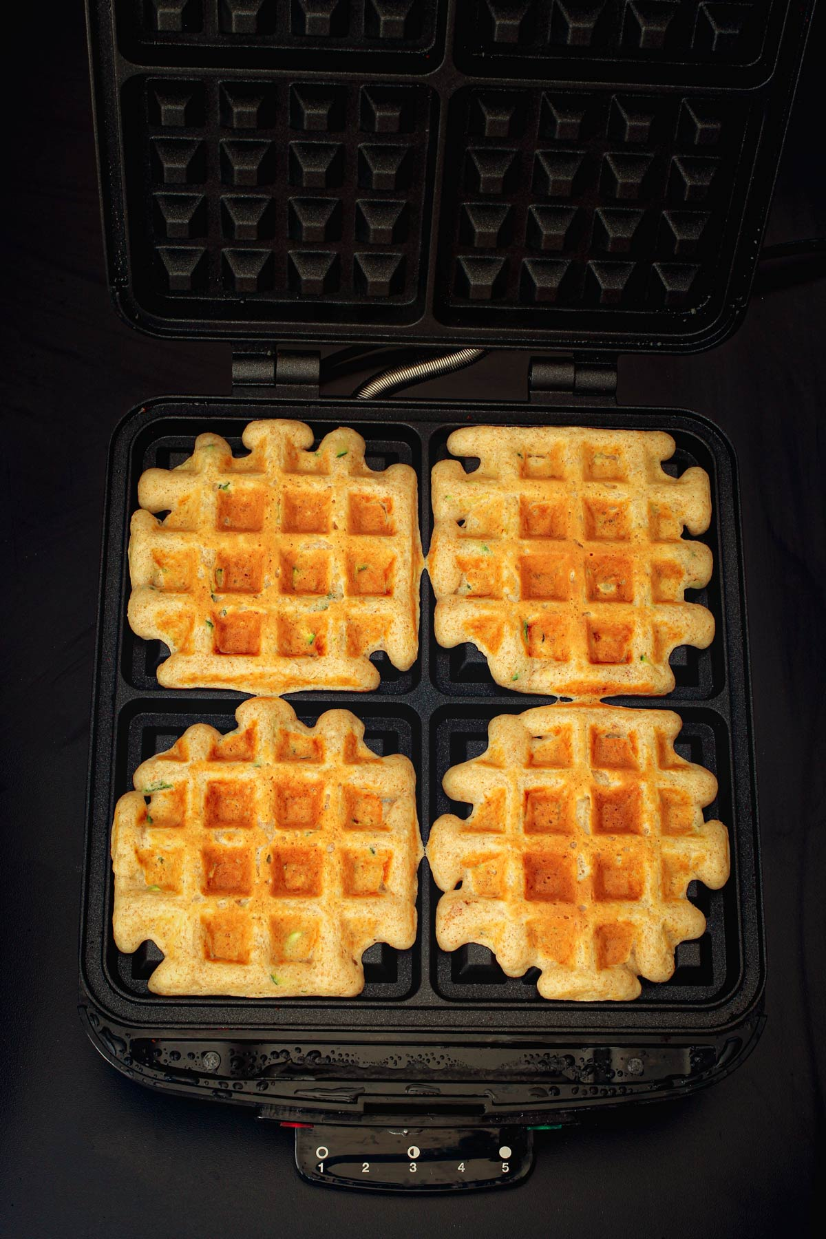 cooked waffles in open waffle iron.