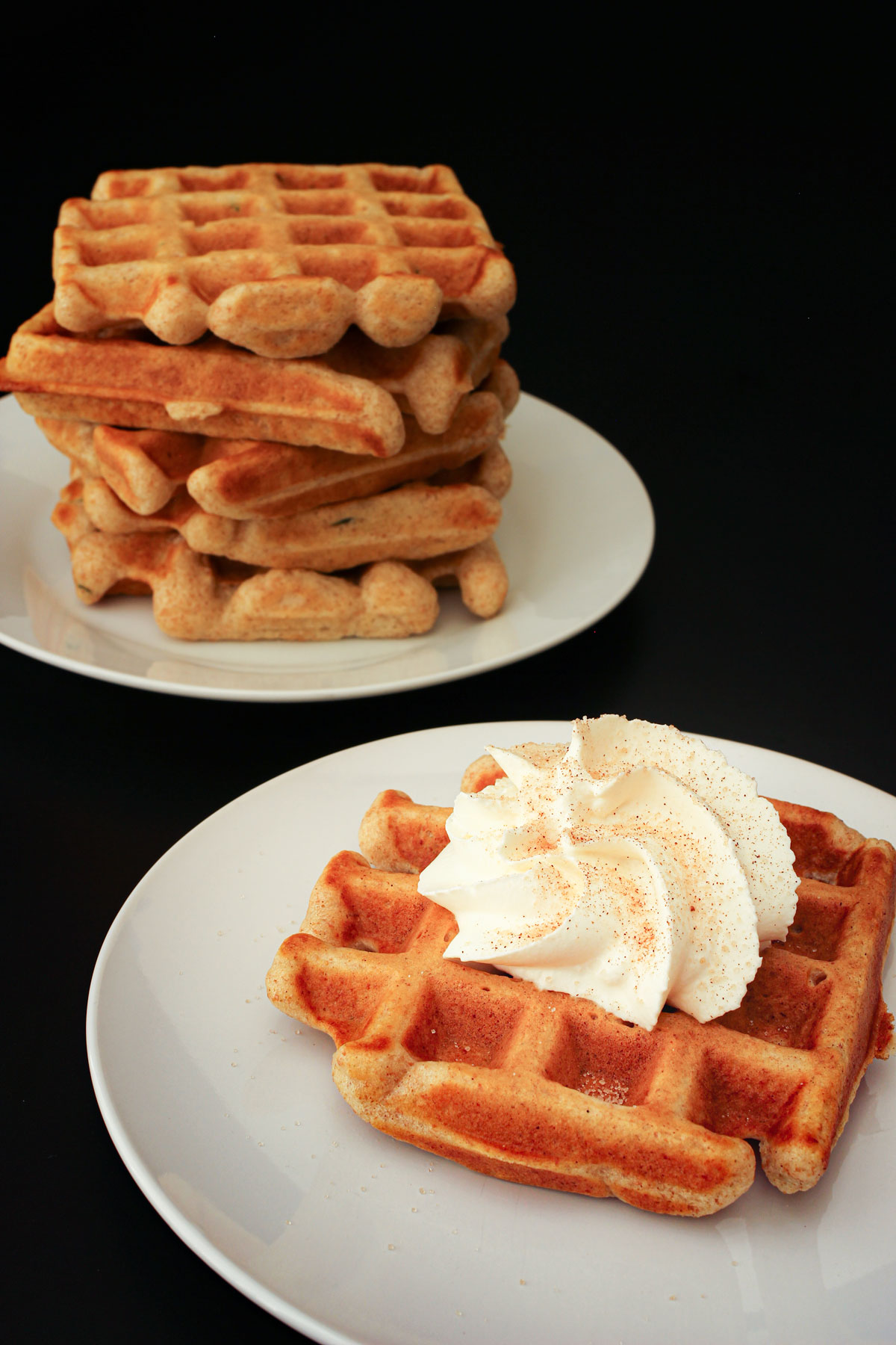 stack of cinnamon waffles next to a plate with a single waffle topped with whipped cream and cinnamon sugar.