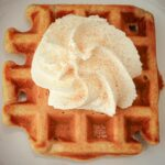 overhead shot of cinnamon waffle topped with whipped cream and cinnamon sugar.