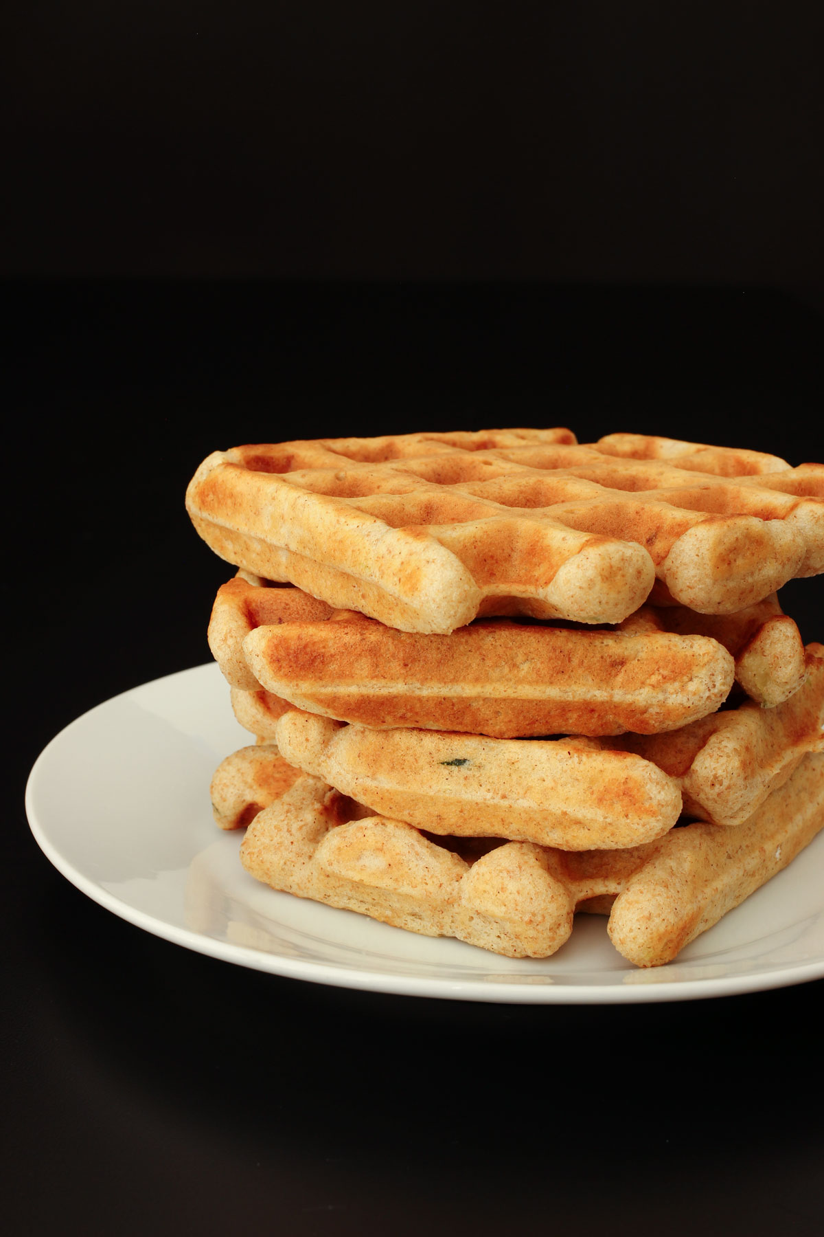 cooked cinnamon waffles stacked on a white plate.