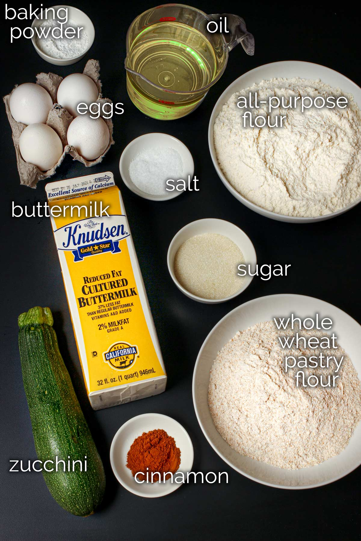 ingredients for zucchini cinnamon waffles laid out on black table top.
