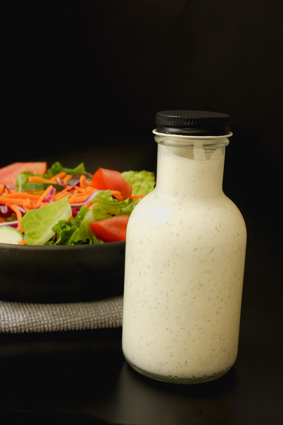 closed bottle of buttermilk dressing next to salad in a black bowl.