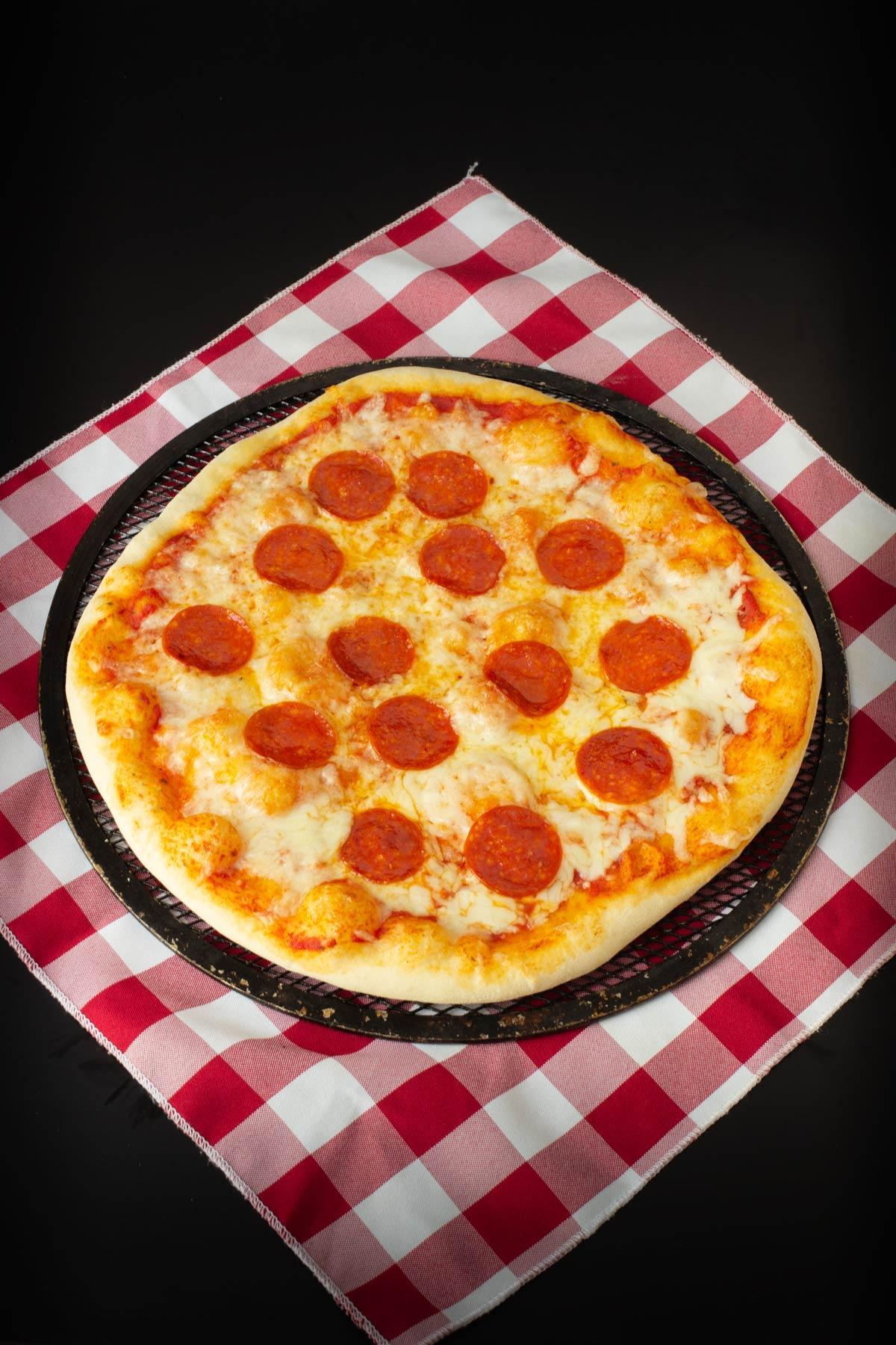 cooked pepperoni sourdough pizza on a checker napkin.