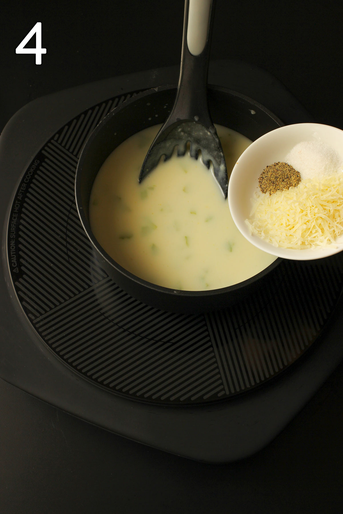 adding cheese and spices to sauce pan.