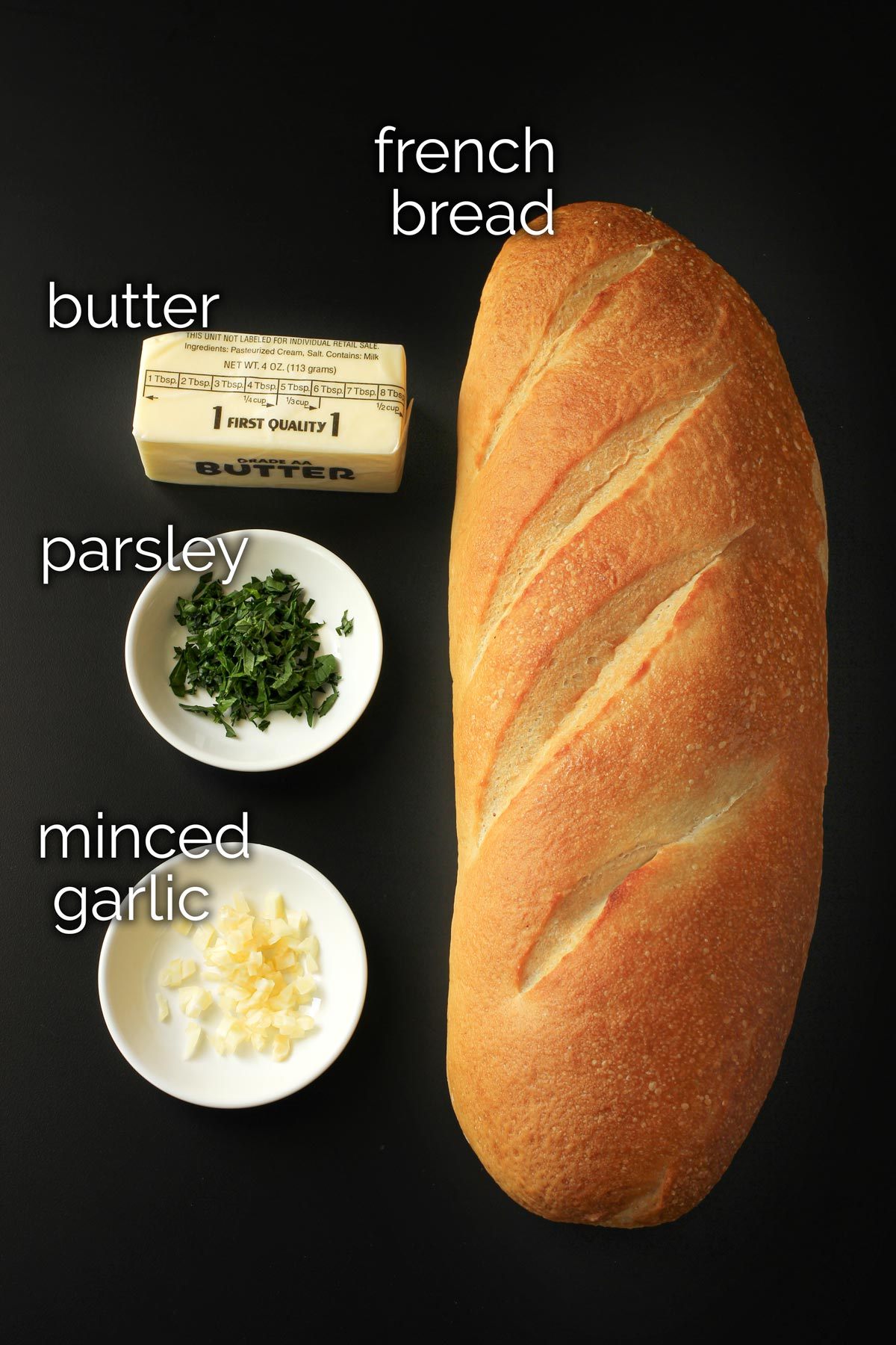 ingredients for frozen garlic bread laid out on black table top.