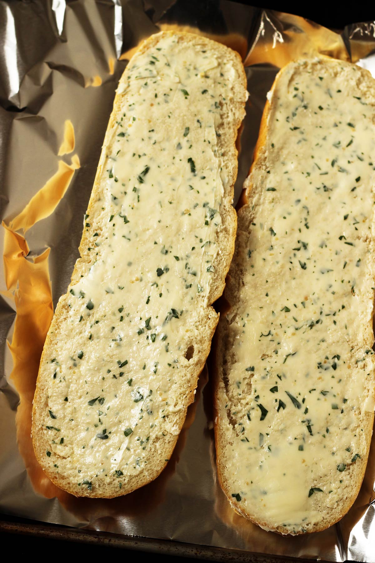 loaf halves spread with garlic butter and placed on aluminum foil.