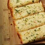 loaf of toasted frozen garlic bread, cut into slices on cutting board with scattered crumbs.
