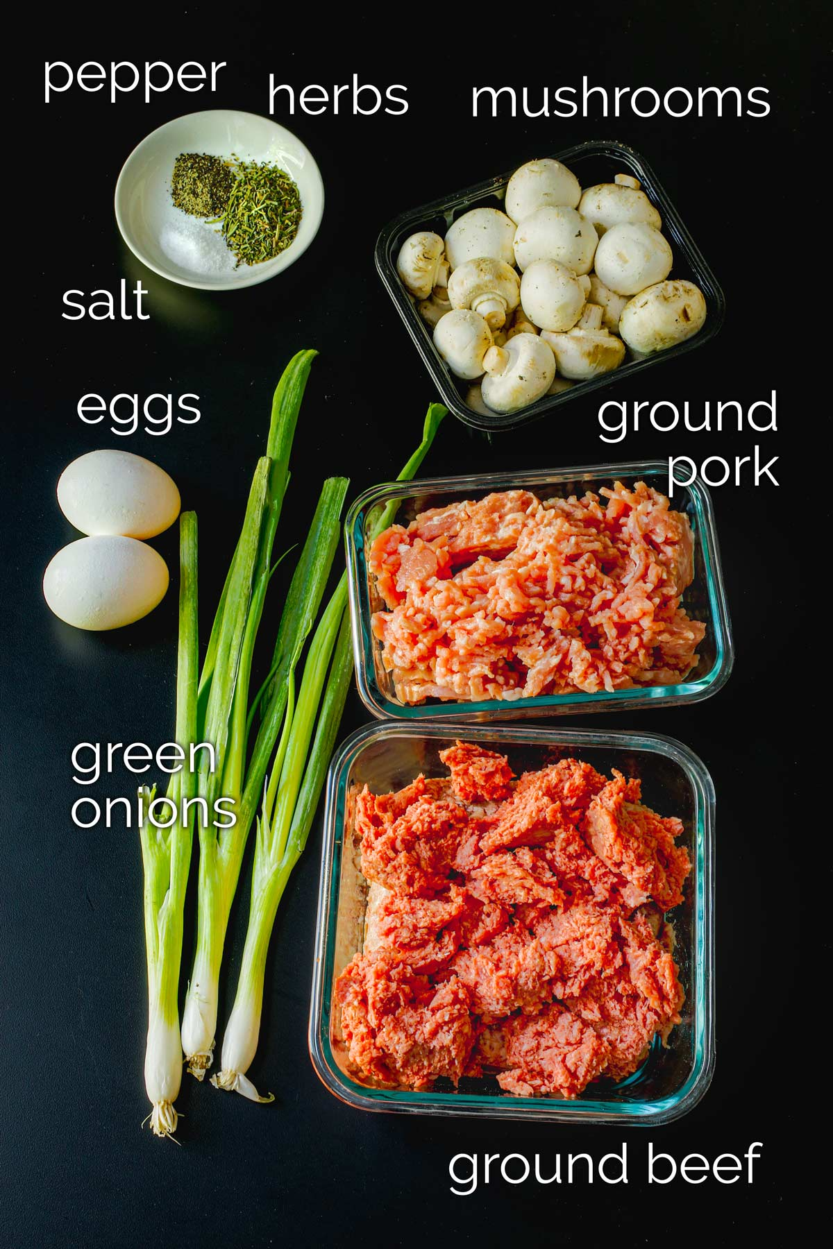 ingredients for gluten-free meatballs laid out on a black table top.