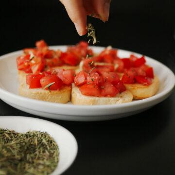 hand sprinkling herbes de provence on plate of bruschetta.