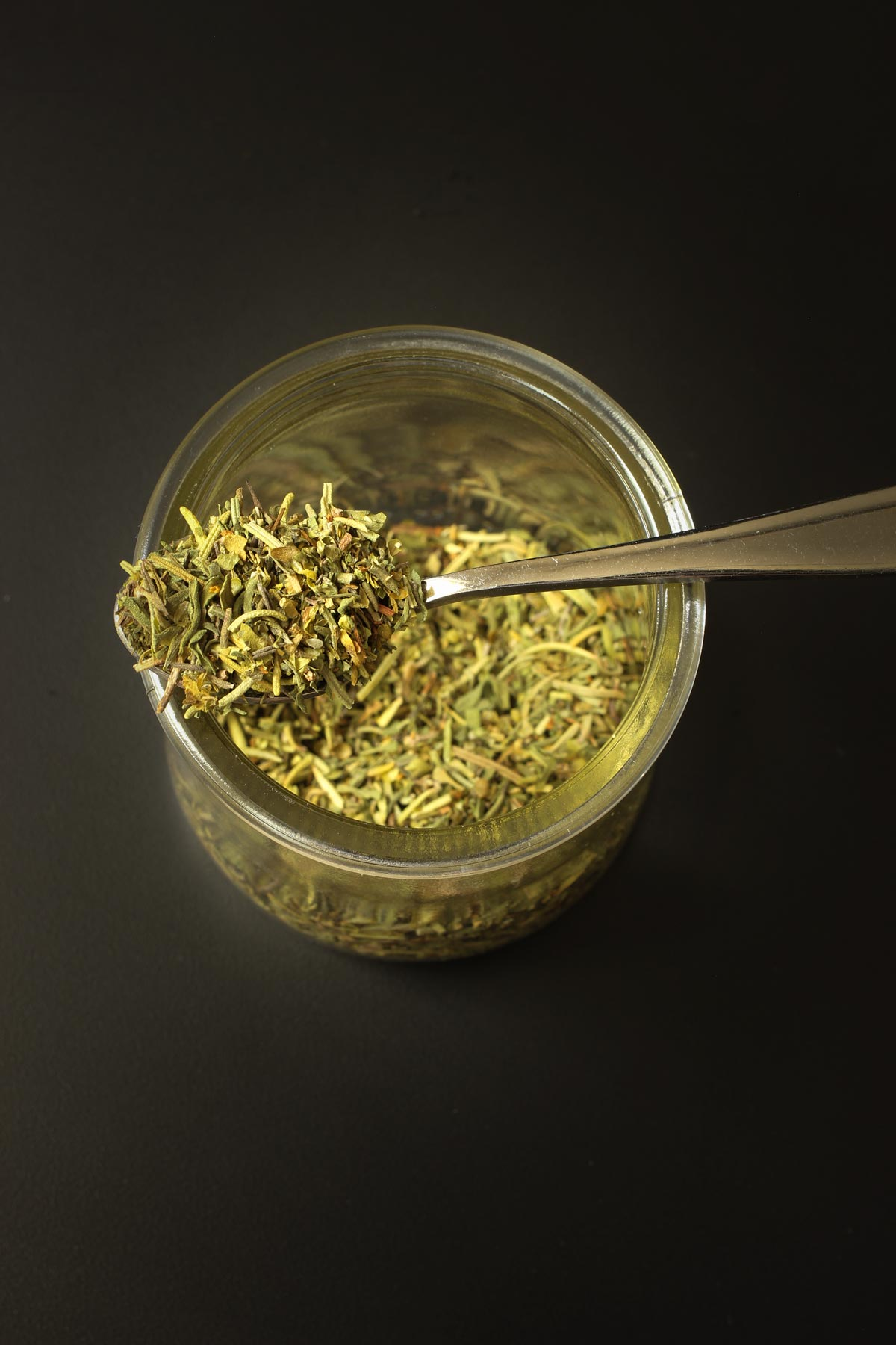 small spoon of herbes resting atop glass jar of more herbes.