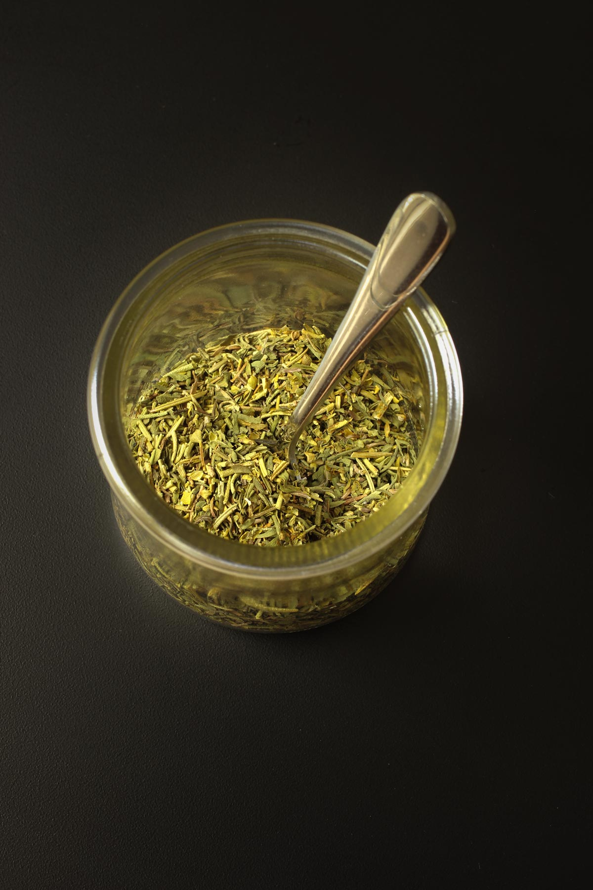 small spoon in glass dish of herbes for mixing the blend.