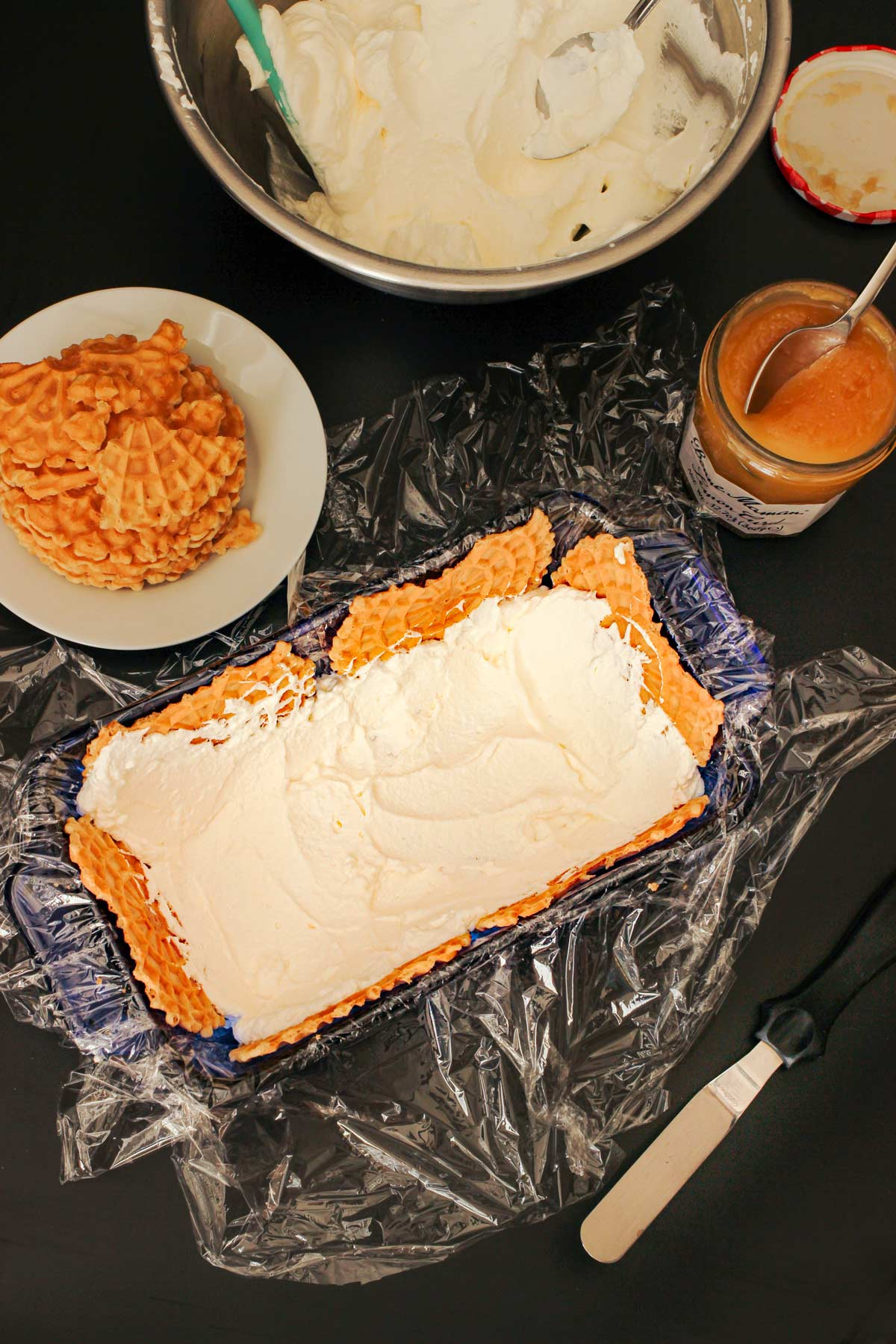 a layer of whipped cream spread over the pizzelles in the pan.