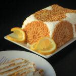 lemon ice box cake on white platter with lemon slices and a slice of cake on a dish.