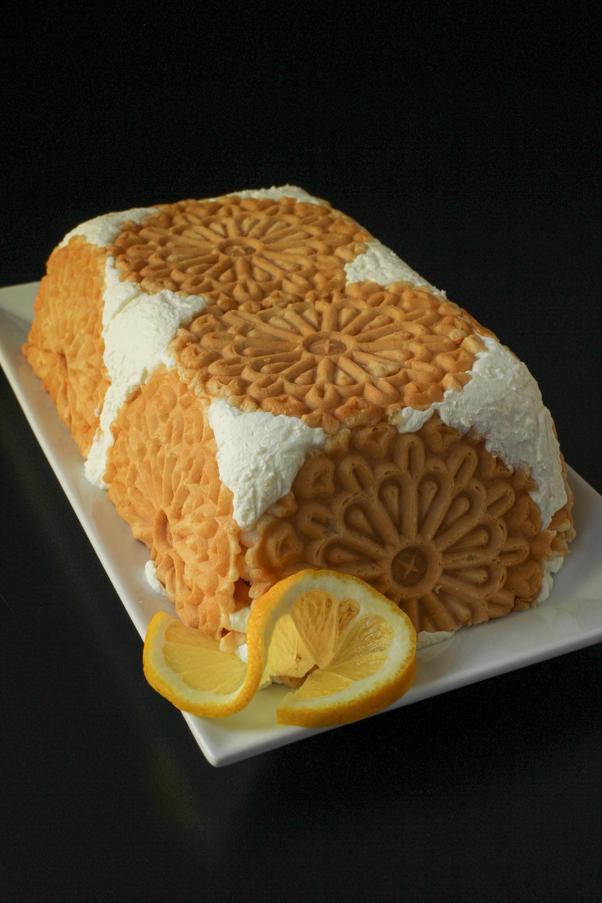 loaf-shaped lemon ice box cake on rectangular platter with lemon slice garnish.