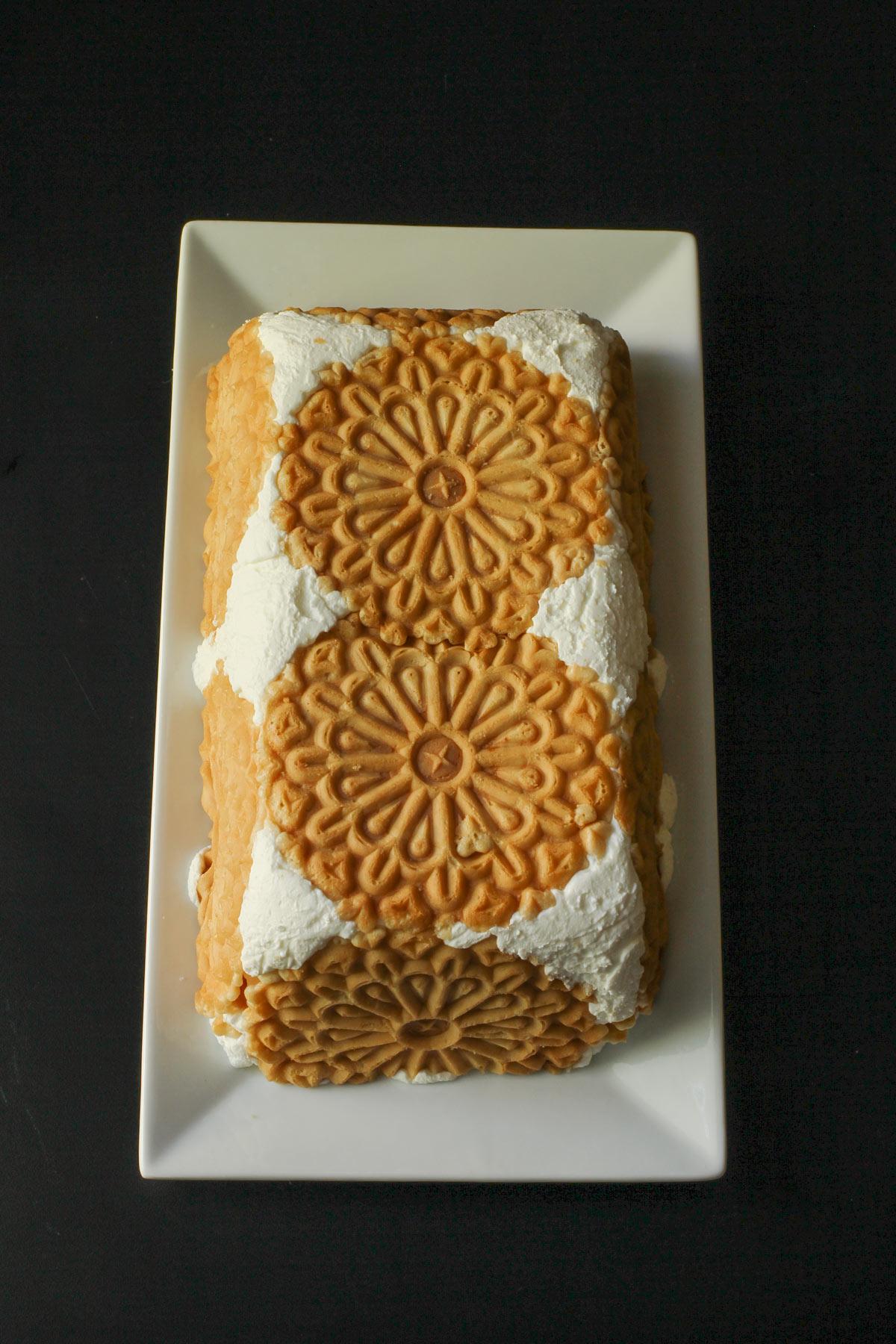 fully unwrapped lemon icebox cake on white platter.