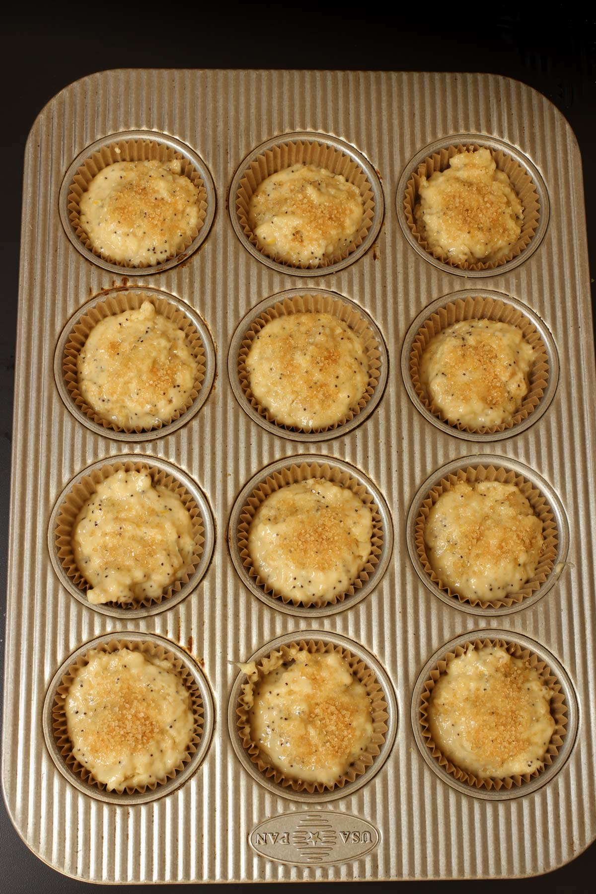 muffin batter topped with coarse sugar ready to bake.