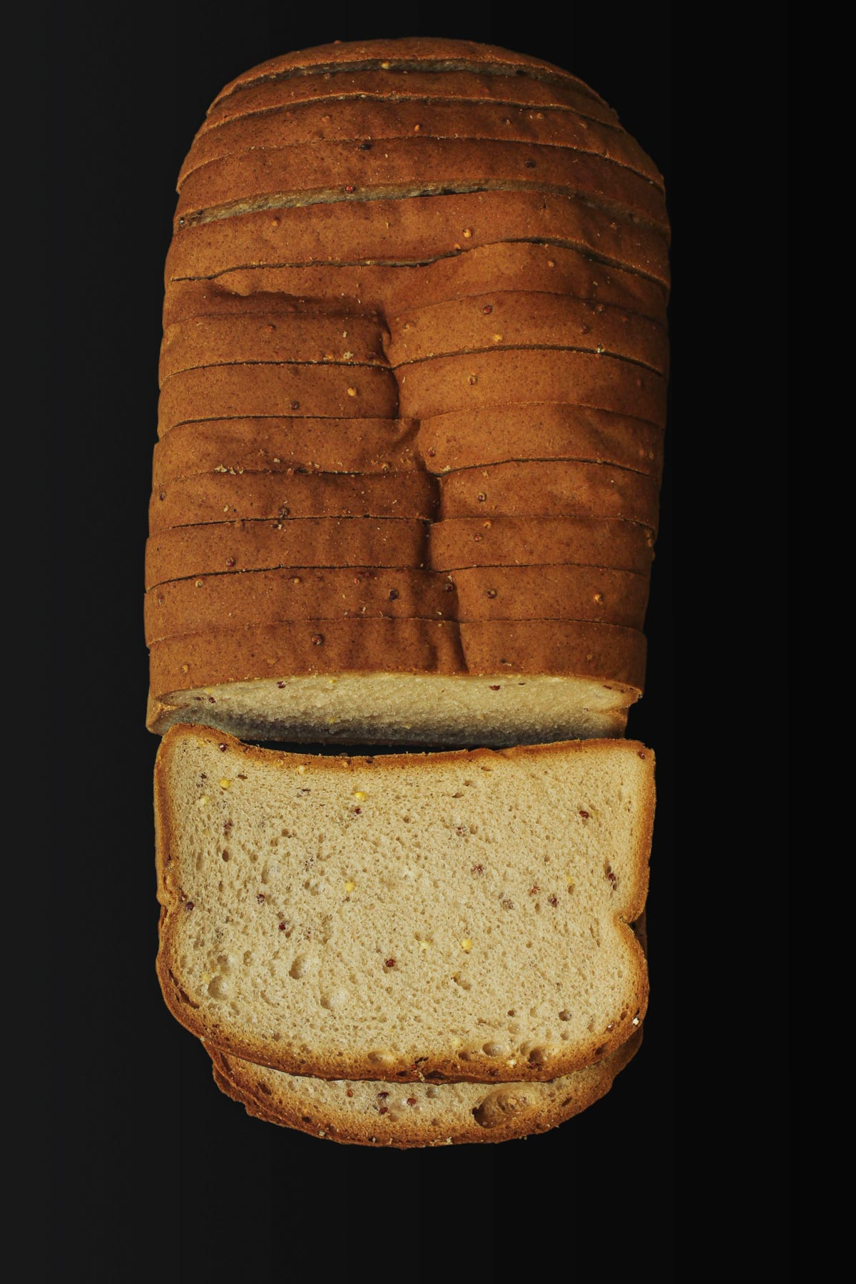 loaf of gluten free sandwich bread out of packaging on black table top.