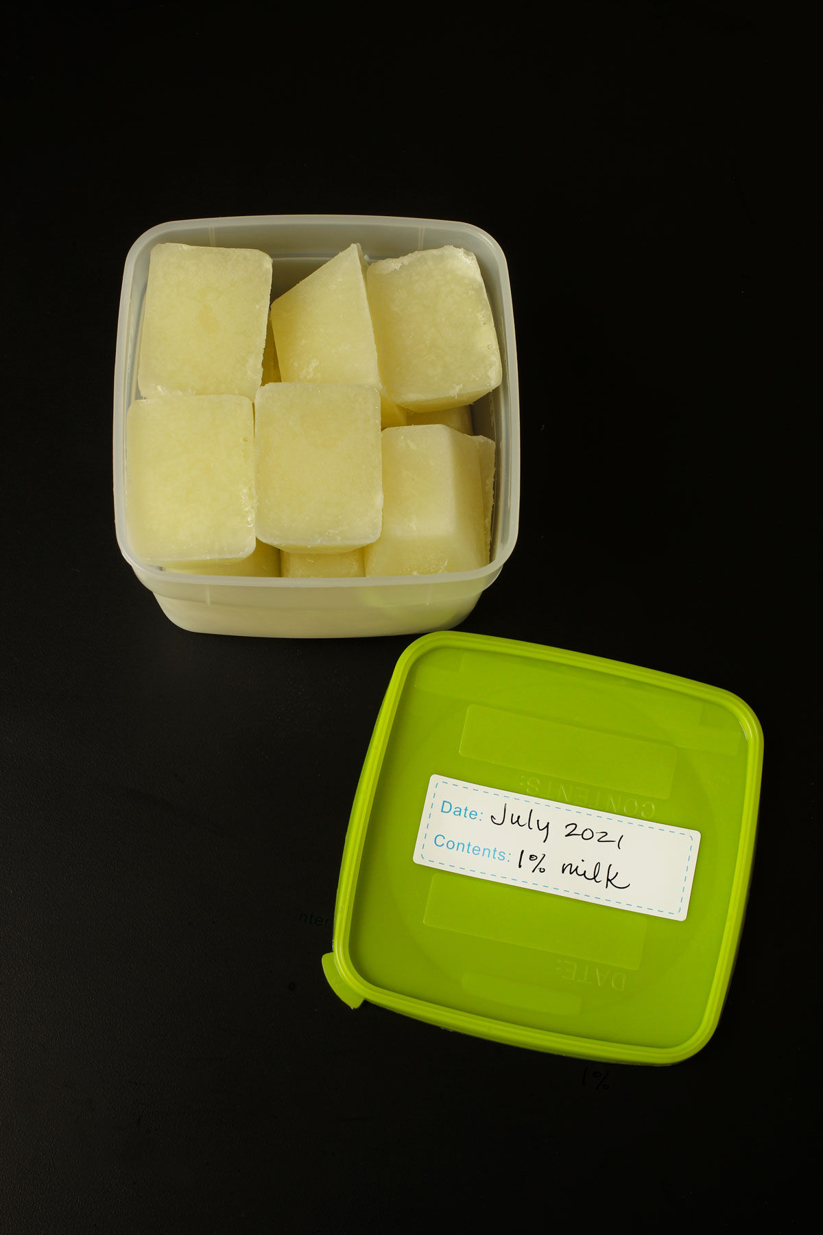 frozen milk cubes in plastic square freezer container with lid with label.