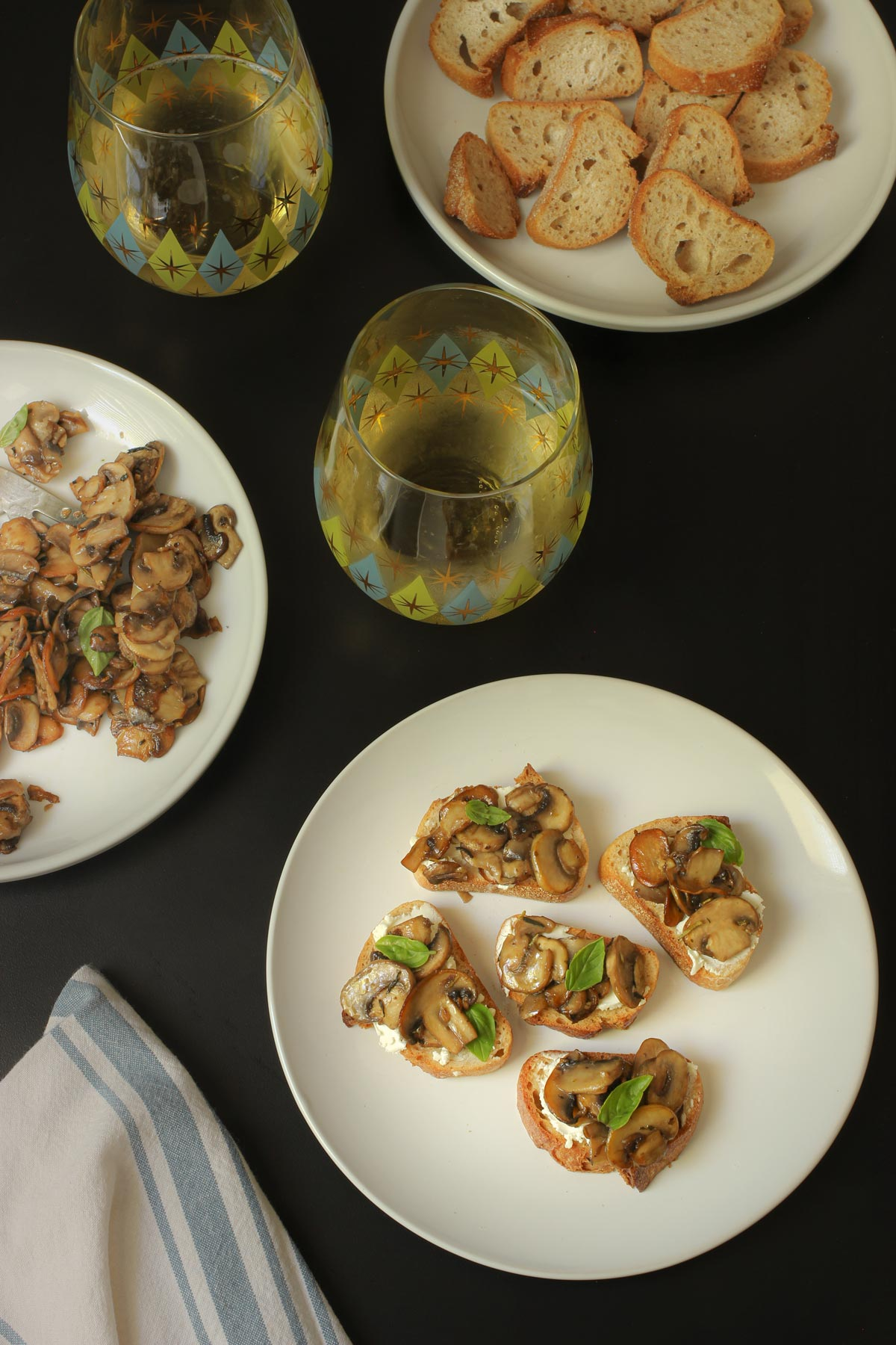 sauteed mushrooms on toast with goat cheese on table with glasses of prosecco.