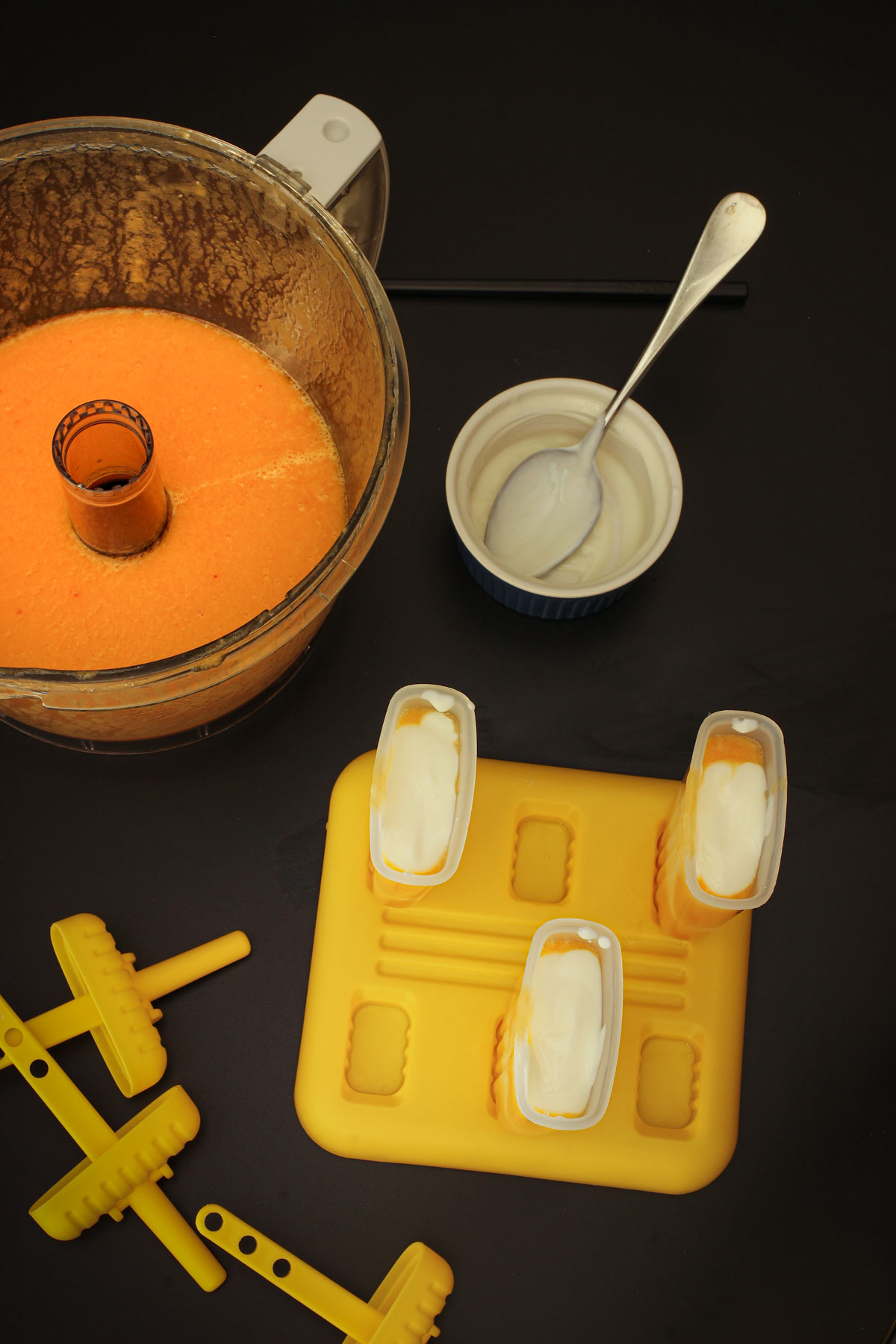 layering yogurt and fruit puree in popsicle molds.