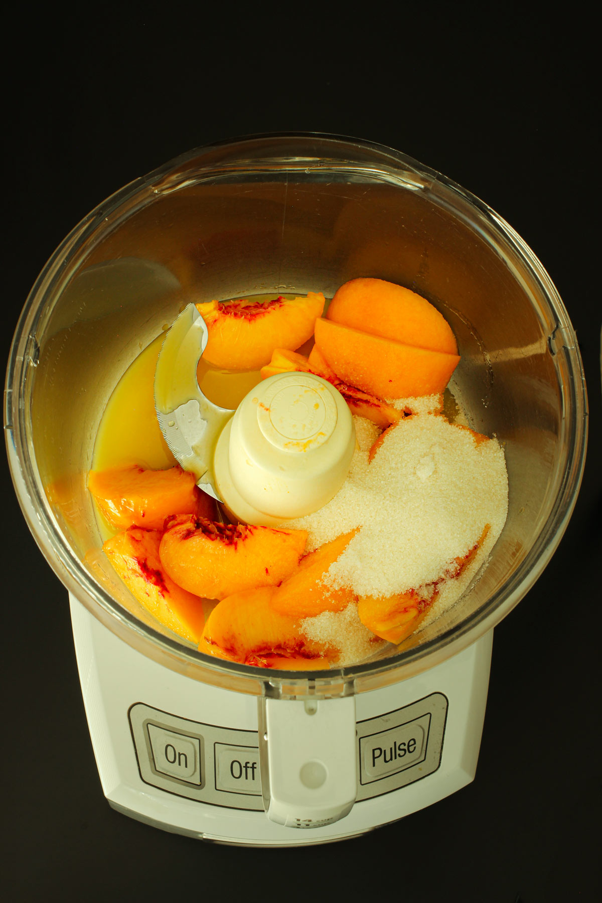 peaches, sugar, and juice in food processor bowl fitted with a metal blade.