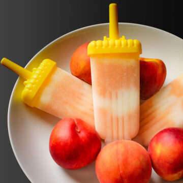 peach yogurt popsicles in their molds in a large white bowl of peaches.